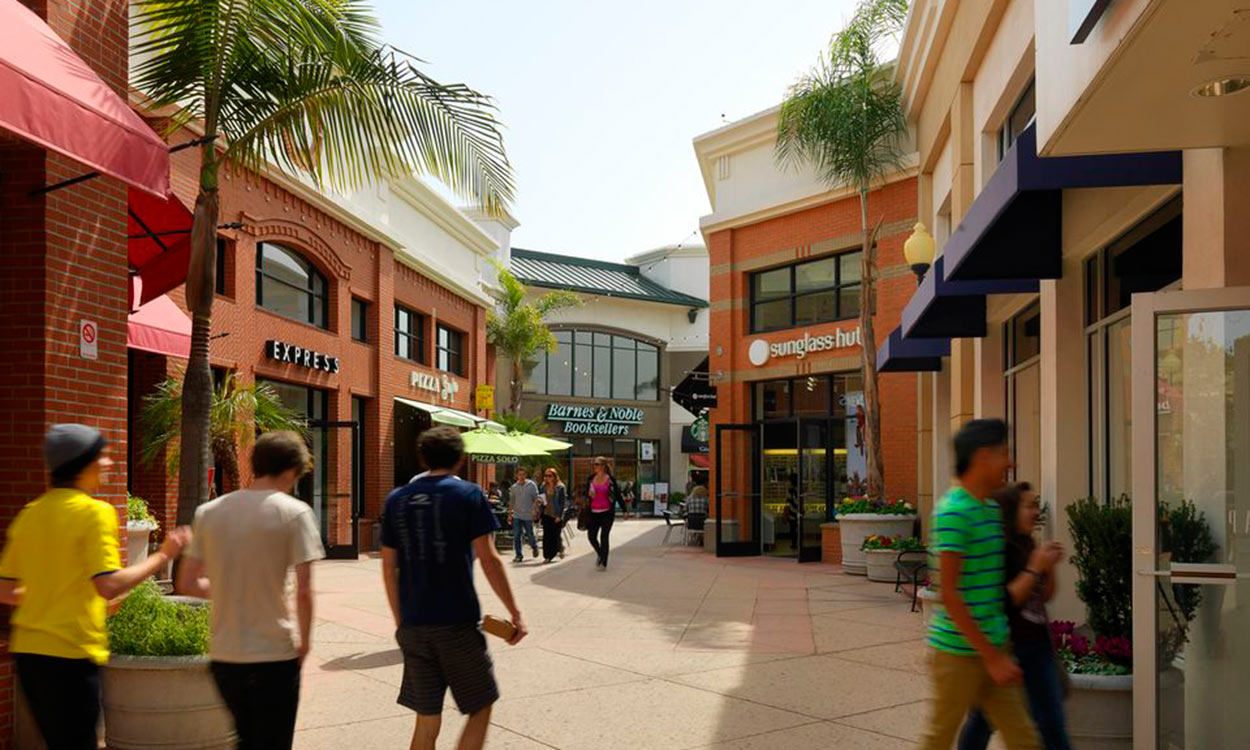 Pedestrians walking along breezeway lined with storefronts at Downtown Centre