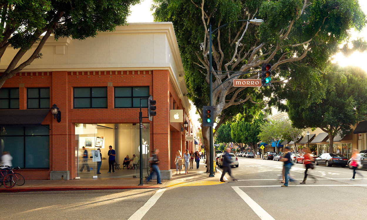The Apple Store storefront with pedestrians on sidewalk and crossing street