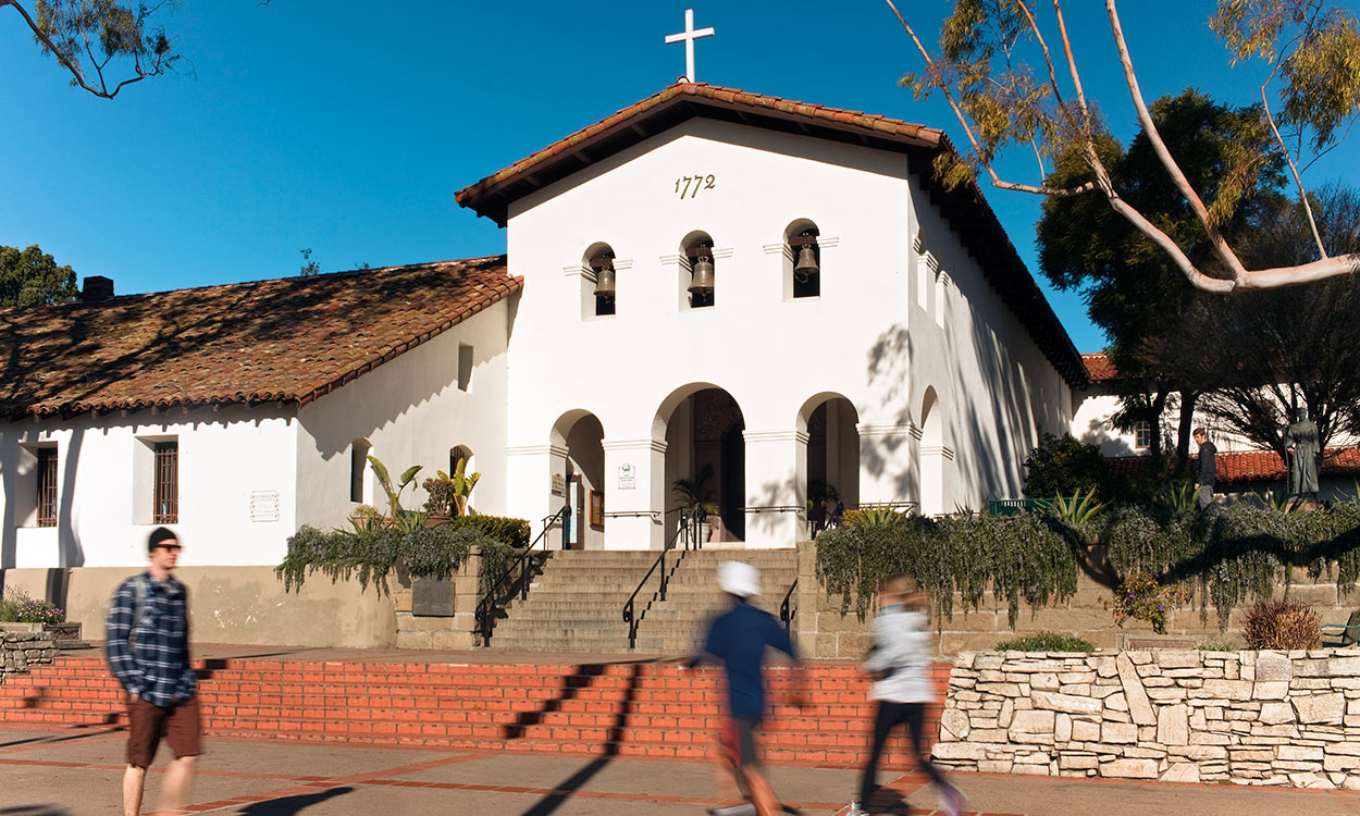 Entrance to San Luis Obispo Mission de Tolosa with pedestrian and joggers on sidewalk in foreground