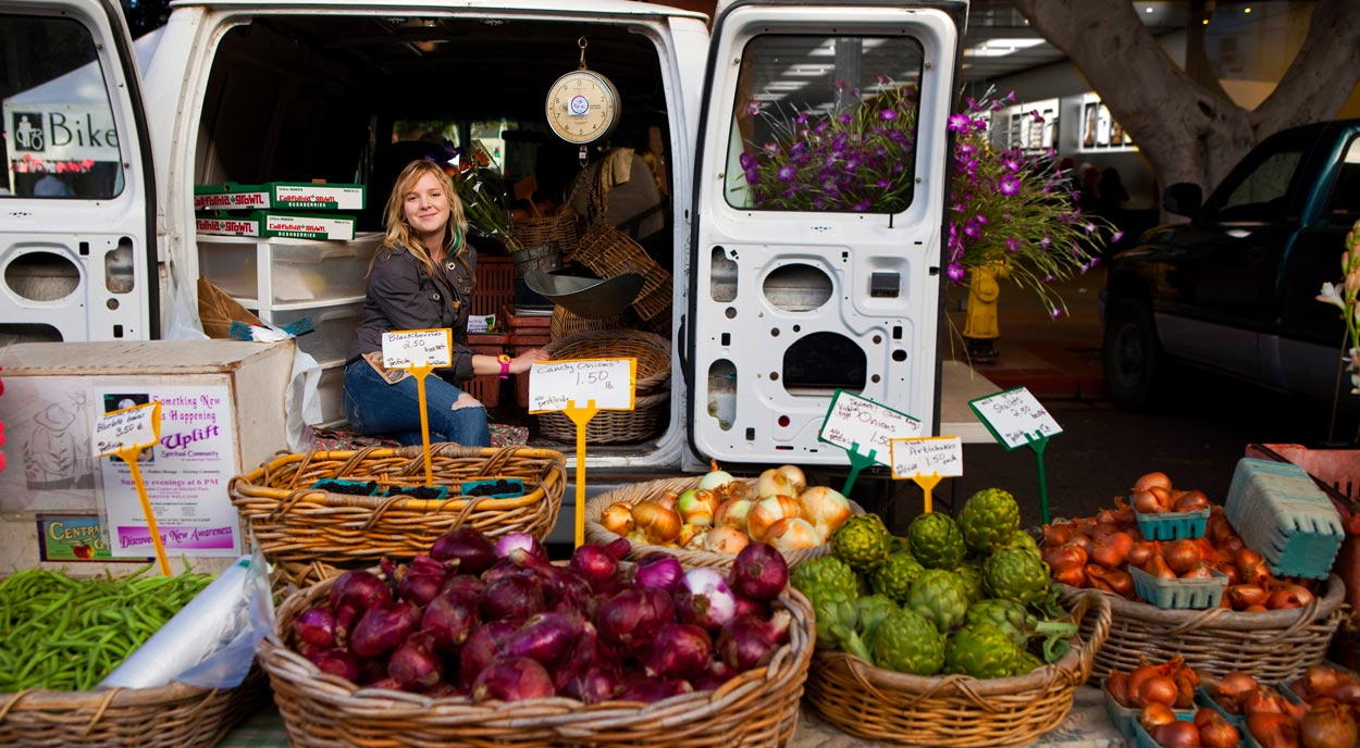 Woman working at farmers market sitting on tailgate of van with baskets of vegetables on a table in front of her