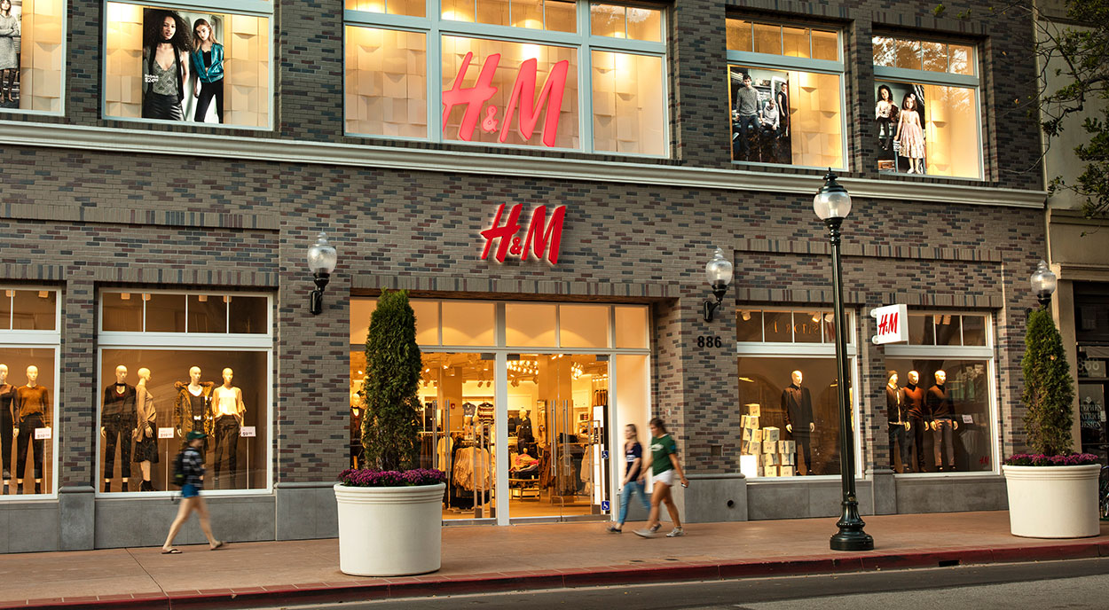 H&M storefront with pedestrians on sidewalk