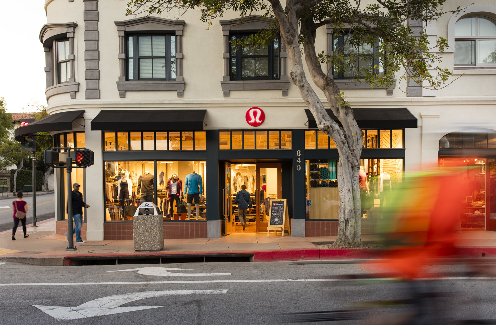 lululemon athletica storefront with pedestrians on sidewalk and bicyclist zooming by in street