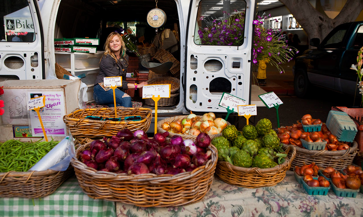 Woman working at Farmers Market seated on tailgate of van with baskets of vegetables in baskets on table in foreground