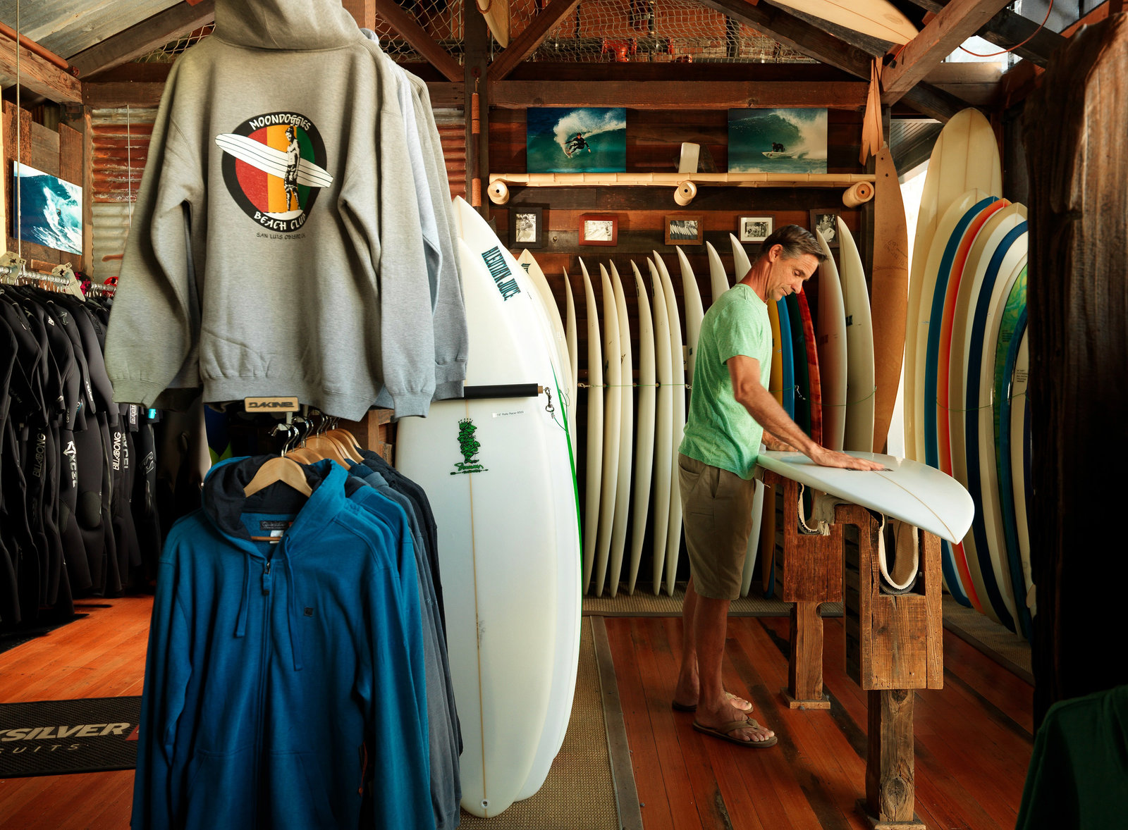 Interior of Moondoggies Surf Shop with man shaping surfboard and racks of surfboards along walls